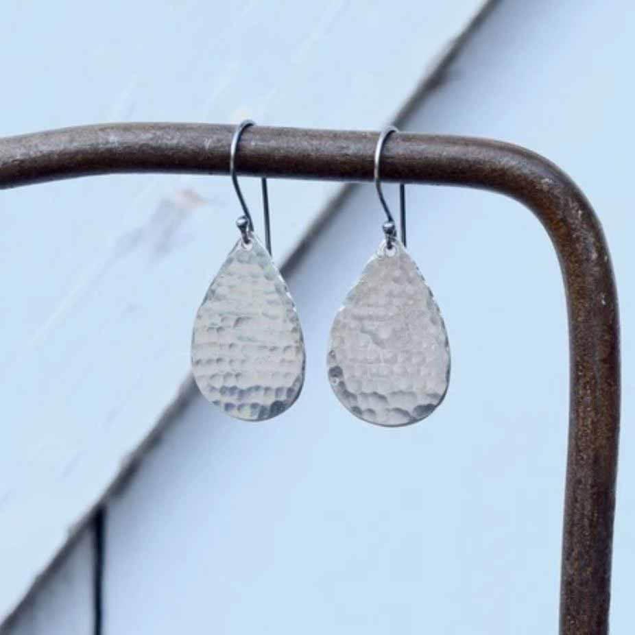 Silver teardrop earrings hanging on brown pipe